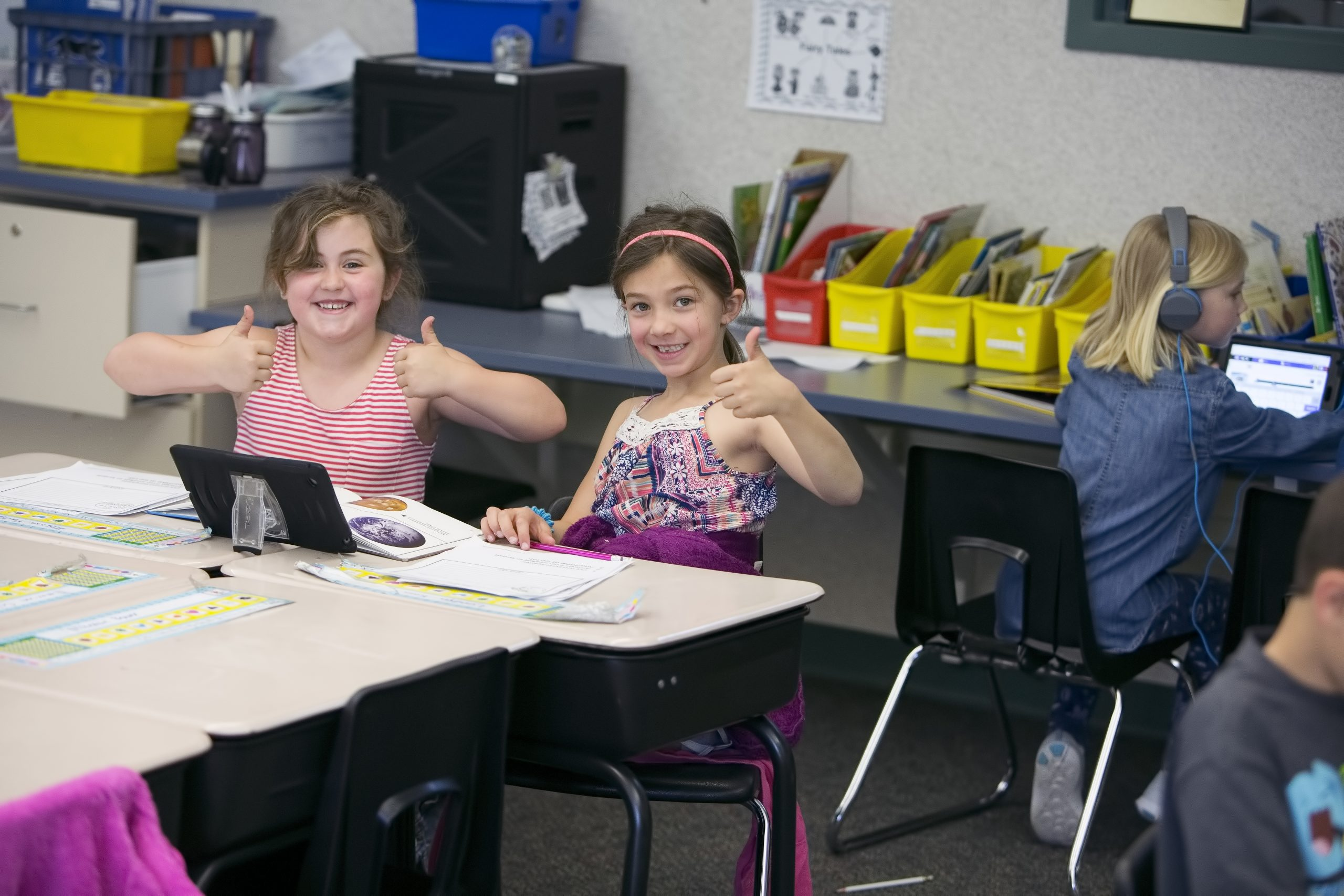 Two female students giving a thumbs up as they work collaboratively.